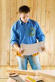 Carpenter looks on blueprint — Stock Photo