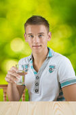 A guy holding glass of water — Stock Photo