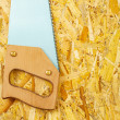 Handsaw on plywood — Stock Photo #23071460