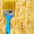 Single paintbrush on plywood - Stock Photo