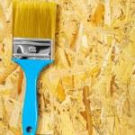 Single paintbrush on plywood — Stock Photo