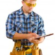 Construction worker writing in paperclip - Stock Photo