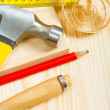 Hammer pencil and ruller on wooden board - Stock Photo