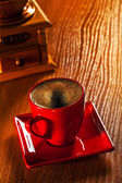 Cup of cappuchino and coffee grinder on wooden board — Stock Photo
