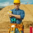 A contractor with theodolite on building place — Stock Photo