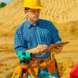 A contractor with theodolite writing in clipboard — Stock Photo