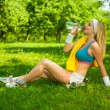Blonde on grass drinking water — Stock Photo