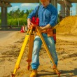 Construction worker adjusting theodolite — Stock Photo