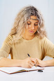 Beautyful blonde wtiting with a ballpoint pen — Stock Photo