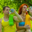 A men and female drinking water from bottles — Stockfoto