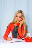 A beautyful blonde at the table with thelephone — Stock Photo