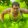 Young man doing press ups on the grass — Stock Photo