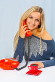 Blonde with telephone at table — Stock Photo