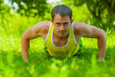 Young man doing press ups on the grass — Stock fotografie