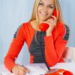 A smiling blonde in red dress with phone — Stock Photo
