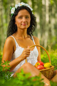 Brunette holding basket with apples — Stock Photo