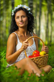 Brunette on grass with apples — Stock Photo
