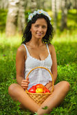 Brunette sitting on grass with basket with apples — Stock Photo