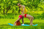 Männer helfen Frauen sich streckenden Muskeln — Stockfoto
