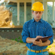 Contractor writing in clipboard — Stock Photo #27835941