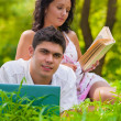 Young couple lying with laptop and book at park — Stock Photo