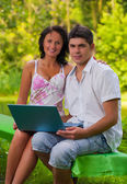 Couple sitting with laptop in park — Stock Photo
