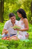 Młoda para siedzi na trawie w parku — Zdjęcie stockowe