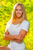 A beautiful blonde on a background of fuzzy foliage — Stock Photo