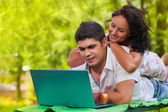 Man and female using laptop — Stock Photo