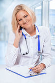 Fryendly female doctor at hte table — Stock Photo