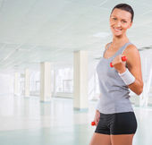Beautiful sportswoman wearing sports clothes holding weights — Stock Photo