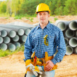 Worker near stack of big pipes — Stock Photo