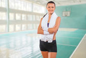 Beautiful fitness girl with towel arms crossed — Stock Photo