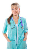 Friendly female doctor with hands in pockets — Stock Photo