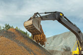 Sand pouring from scoop of excavator — Stock Photo