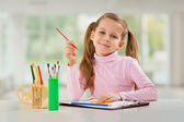 A young girl with pencil sitting at table — Stock Photo