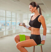 Beautiful female lifting weight and sitting on chair — Stock Photo
