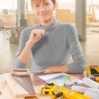 Female worker sitting at table with tools — Stock Photo