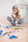 Young female painter sitting on floor — Stock Photo
