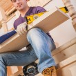 A young worker siiting on step of ladder and holding wooen board — Stock Photo