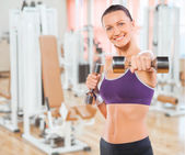 Beautiful feamale exercising with weights in gym — Stock Photo