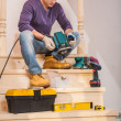 Carpenter sitting on step of wooden ladder — Stock Photo
