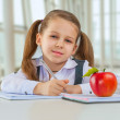 Beautiful litle schoolgirl sitting at table — Stock Photo #41844259