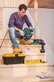 Carpenter sitting on step of wooden ladder — Stock Photo