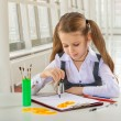 Beautiful litle schoolgirl siiting at table and drawing with com — Stock Photo #42748087