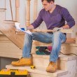 Young worker sitting on wooden ladder and loking in blueprint — Stock Photo