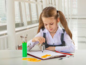 Beautiful litle schoolgirl siiting at table and drawing with com — Stock Photo