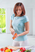 Beautiful female wearing sports clothes slicing carrot — Stock Photo