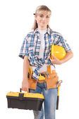 Female wearing working clothes with toolbelt holding hardhat — Stock Photo