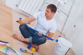 Youg painter sitting on floor — Stock Photo